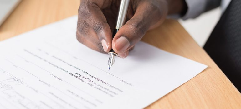 person signing papers when getting moving insurance