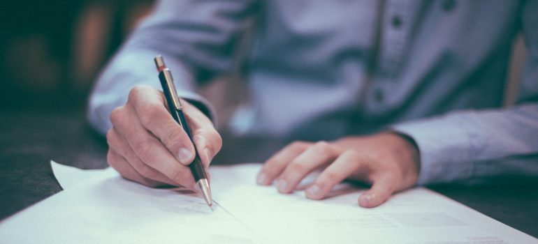 person signing papers with a pen
