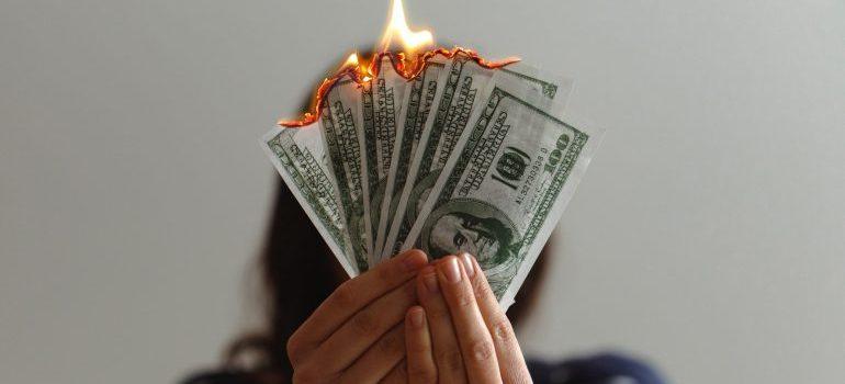 person holding a fan of burning dollar bills