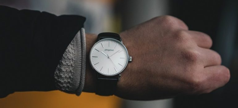 A person wearing a watch - by hiring Des Plaines movers, you are saving time