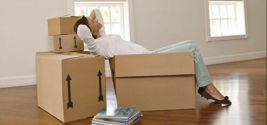 Woman sitting in a moving boxes, inside an empty house