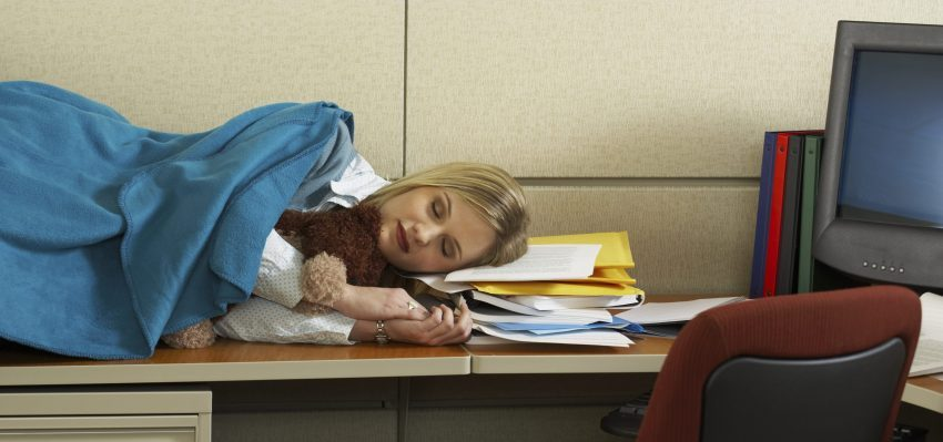 A person sleeping on her work desk