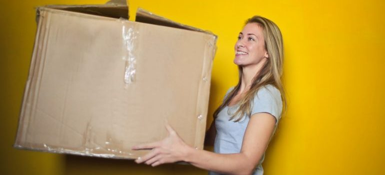 A woman carrying a cardboard box