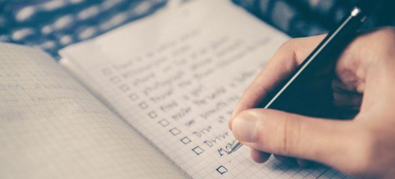 person writing down a checklist