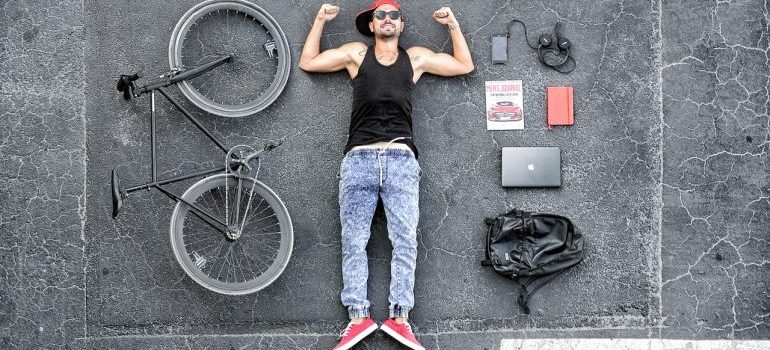 A man lying on the floor with a bicycle and other stuff