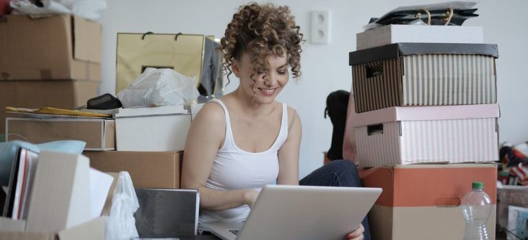 A gilr sitting next to her moving boxes and holding a laptop.