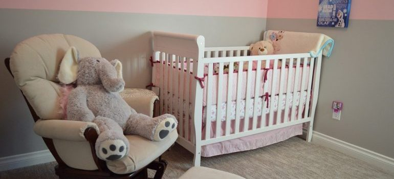 A crib and a chair with a teddy bear