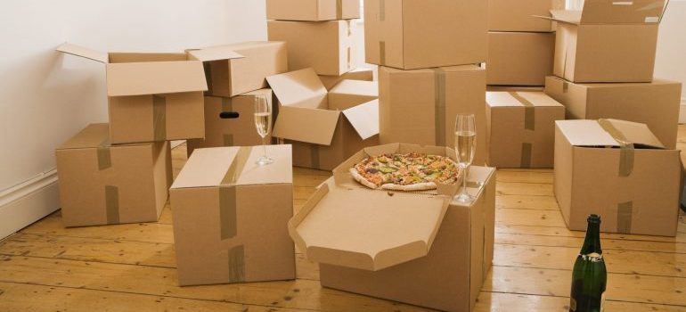 Moving boxes, pizza, and a bottle