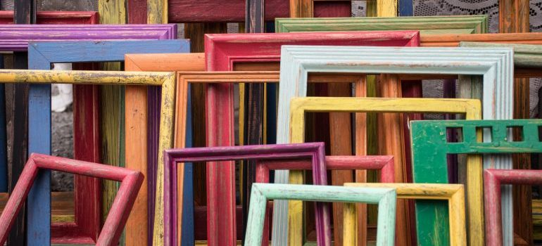 Colorful picture frames stacked against a wall