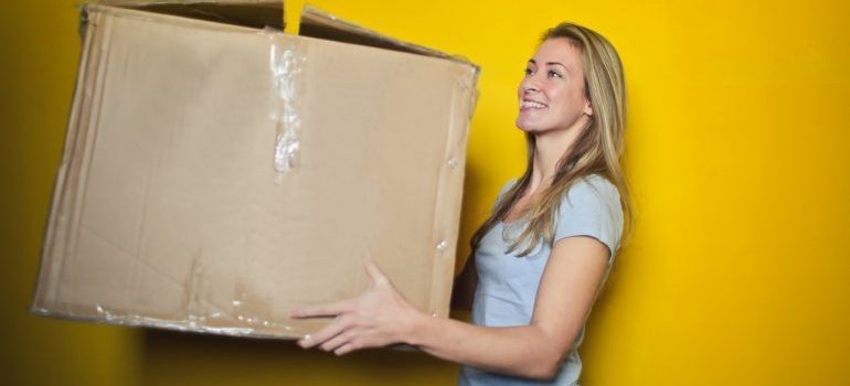 A woman holding a used box not knowing the reasons to avoid used moving boxes