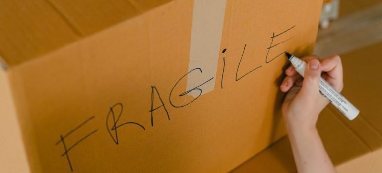 A hand writing on a box