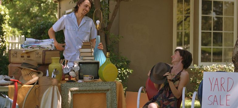 a man and a woman holding a yard sale of items you should leave behind when moving