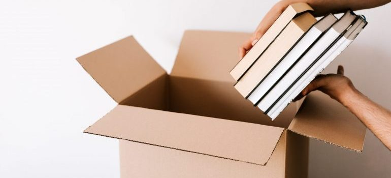 Man packing stack of books in opened cardboard box