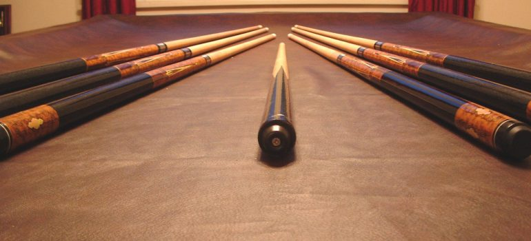 several pool cues lined up on the pool table