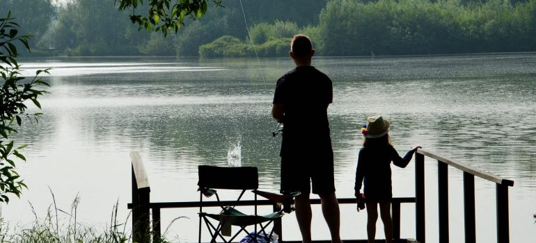 a father and daughter fishing together on a lake