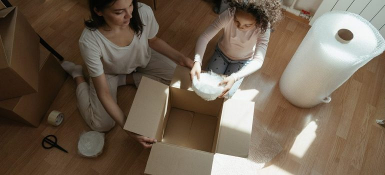 a mom and her daughter pack glasses and dishes for the move in separate boxes