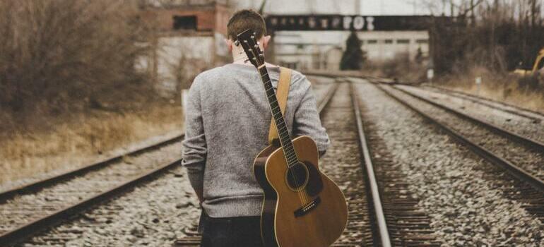 man carrying a guitar
