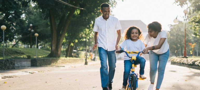 parents teaching their daughter to ride a bycicle in one of the best places for families in Cook County