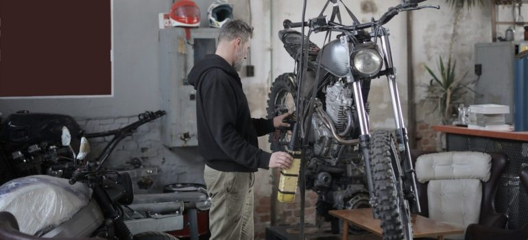 a man in a black hoodie fixing a motorcycle in his garage