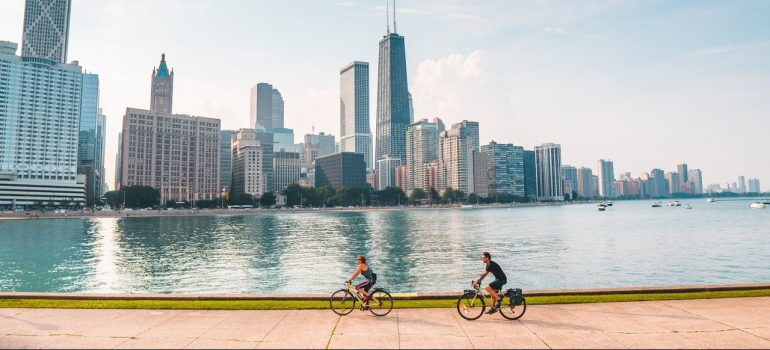 a panoramic view of the city of Chicago with two people riding bicycle near Lake Michigan