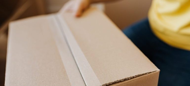Sealing cardboard box with tape