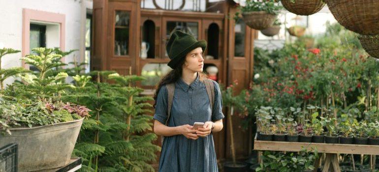A woman standing near green plants