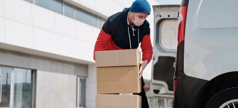 a man packing smaller cardboard boxes inside a van as one of the main differences between residential and commercial moving
