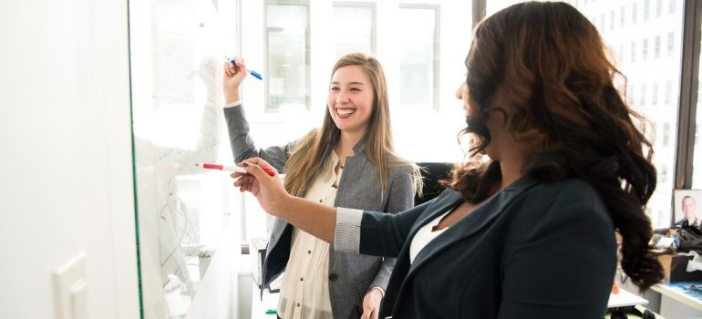 two women planning something in front of a whiteboard