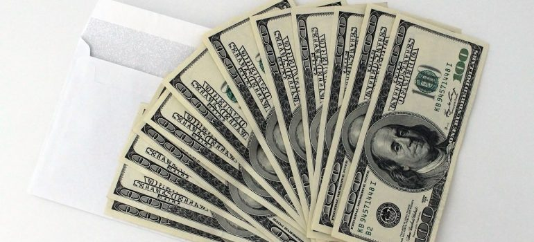a stack of dollars on a white table representing an amount one sould spend for a first home in Skokie