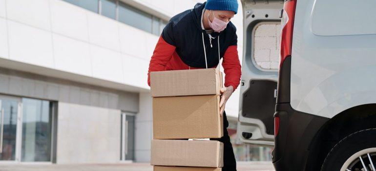 a man placing cardboard boxes inside a white van