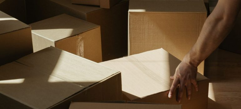 a man pushing cardboard boxes on a pile to avoid some of the most common unpacking mistakes
