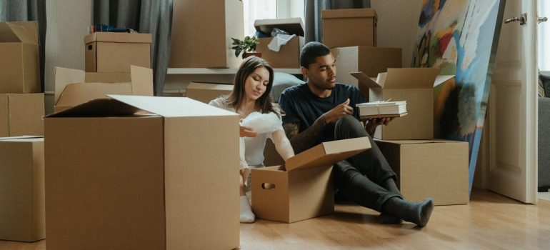 a couple sitting on the floor while unpacking cardboard boxes