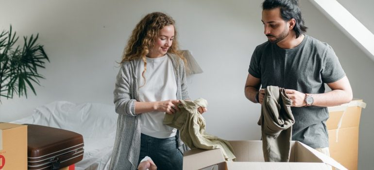 a couple pulling clothes out of a cardboard box