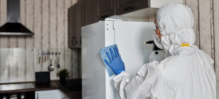 a person wearing a protective suit disinfecting a fridge