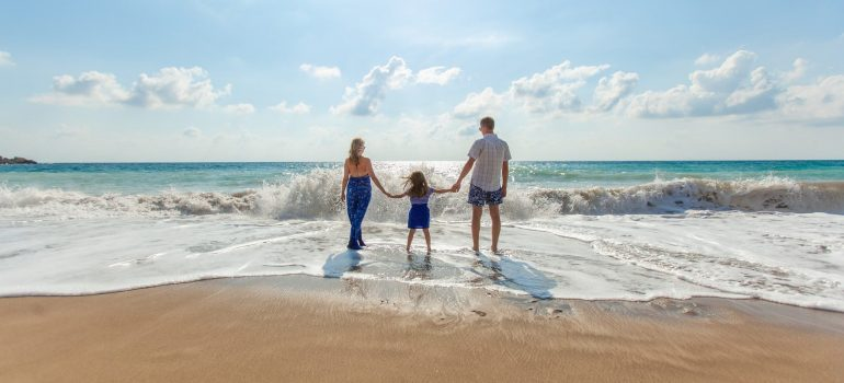 two parents and a child standing on the shore as one of things to do when moving your family to Evanston