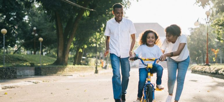 Father and mother teach a child to ride a bicycle