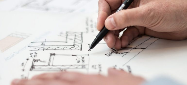 a person drawing house plans on paper as should you when you personalize your Park Ridge home