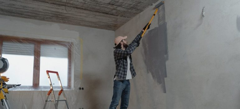 a man painting the walls in a home