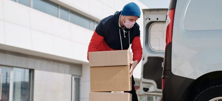 a man putting boxes in the van - moving supplies for your Niles relocation