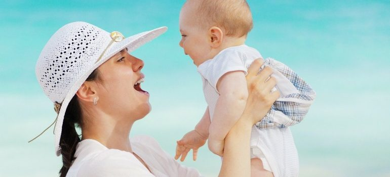 A woman dressed in white, with a white hat, enjoys being able to organize a stress-free relocation with a newborn, which she holds in her hands.